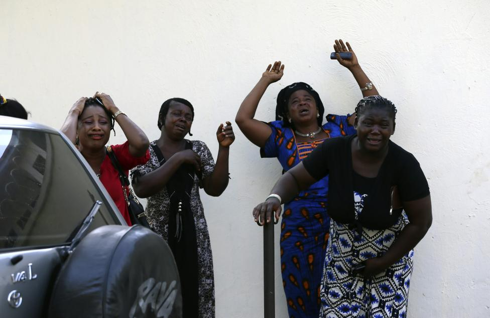 Bystanders react as victims of a bomb blast arrive at the Asokoro General Hospital in Abuja