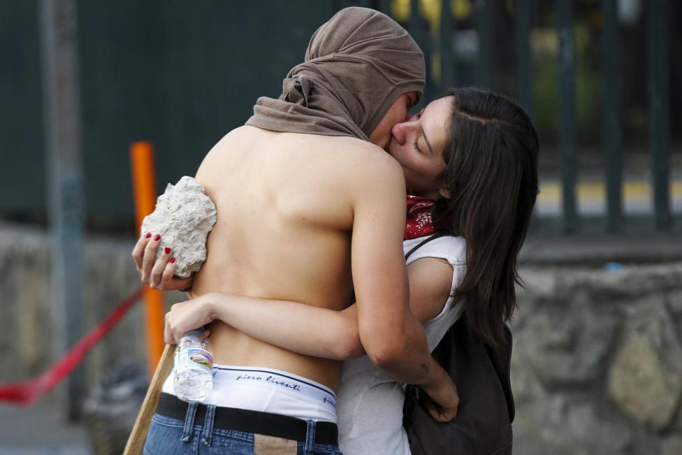 Anti-government protesters kiss during a protest in Caracas
