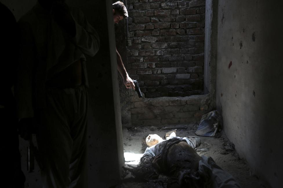 An Afghan resident points his weapon at the dead body of an unidentified militant, as a way of showing his hatred for insurgents, at a building after an attack in Kabul
