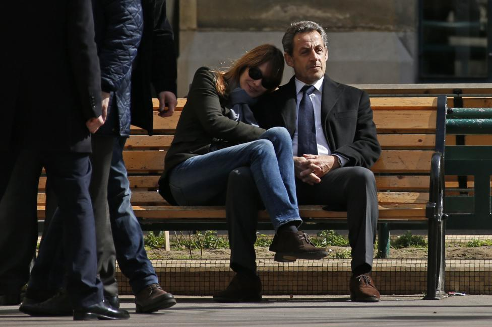 Former French President Nicolas Sarkozy sits on a bench with his wife and singer Carla Bruni-Sarkozy after voting at a polling station in the first round in the French mayoral elections in Paris