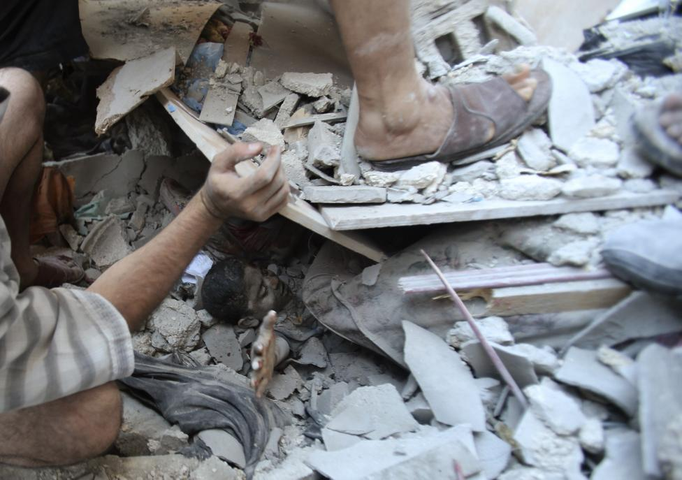 Palestinians rescue Mahmoud al-Ghol from under the rubble of a house in Rafah in the southern Gaza Strip