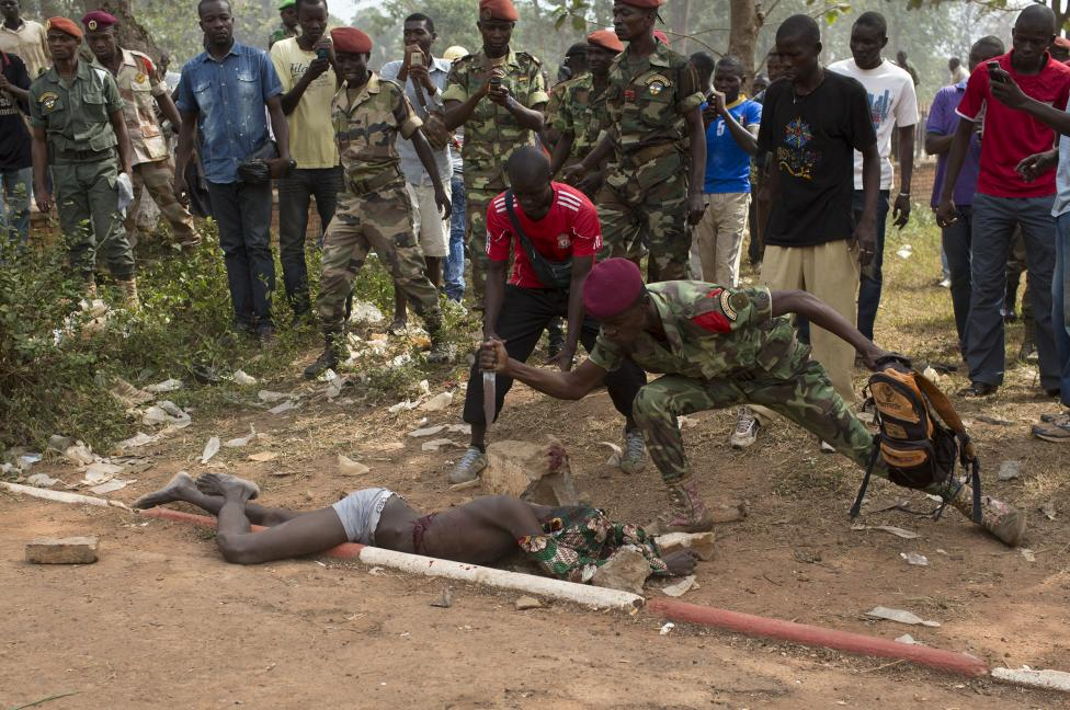 A Central African Army soldier stabs the corpse of a man, who was killed as he was accused of joining the ousted Seleka fighters, in Bangui