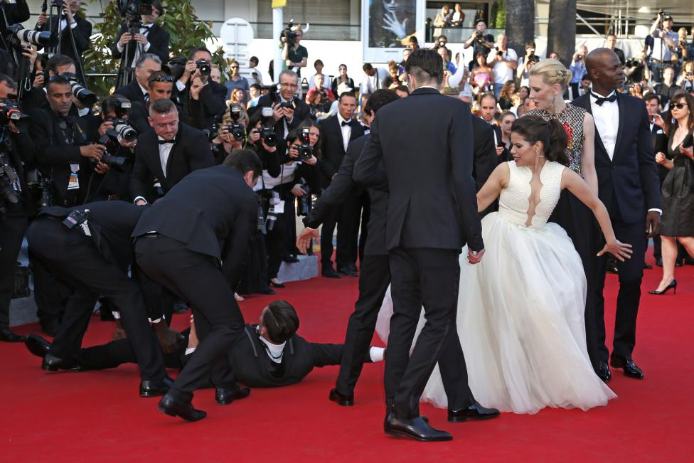 """A man is arrested by security as he tries to slip under the dress of actress America Ferrera as she poses on the red carpet arriving for the screening of the film """"How to Train Your Dragon 2"""" out of competition at the 67th Cannes Film Festival in Cannes"""