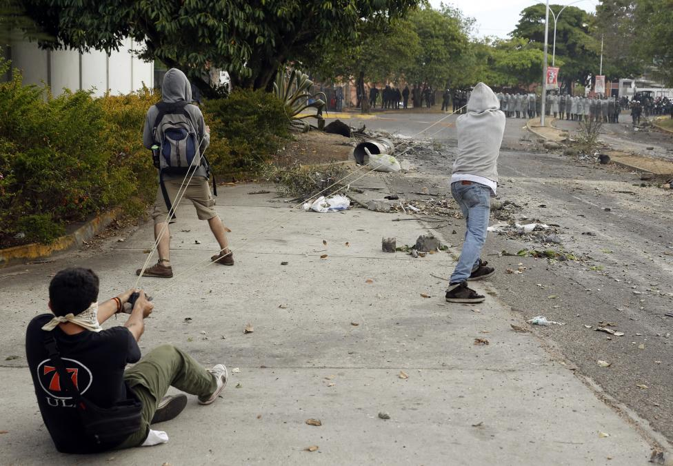 Demonstrators use a slingshot against the National Guard during a protest against Venezuelan President Maduro's government in San Cristobal