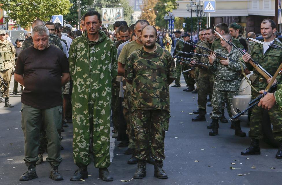 Armed pro-Russian separatists (R) escort a column of Ukrainian prisoners of war as they walk across central Donetsk