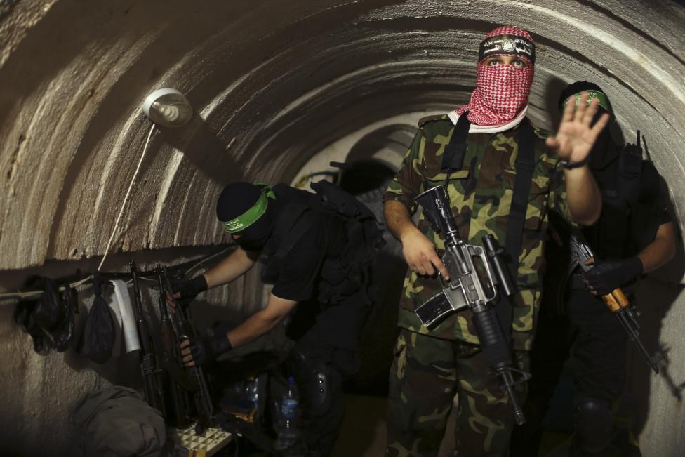 A Palestinian fighter from the Izz el-Deen al-Qassam Brigades, the armed wing of the Hamas movement, gestures inside an underground tunnel in Gaza