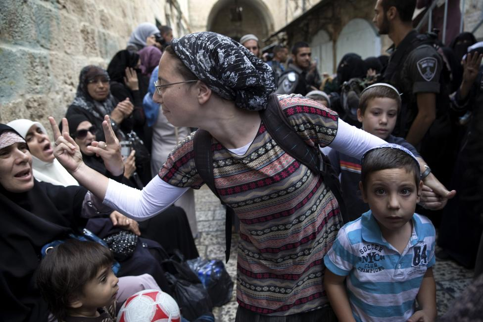 An Israeli woman and a Palestinian woman gesture at one another during a protest by Palestinian women against Jewish visitors to the compound known to Muslims as Noble Sanctuary and to Jews as Temple Mount in Jerusalem's Old City