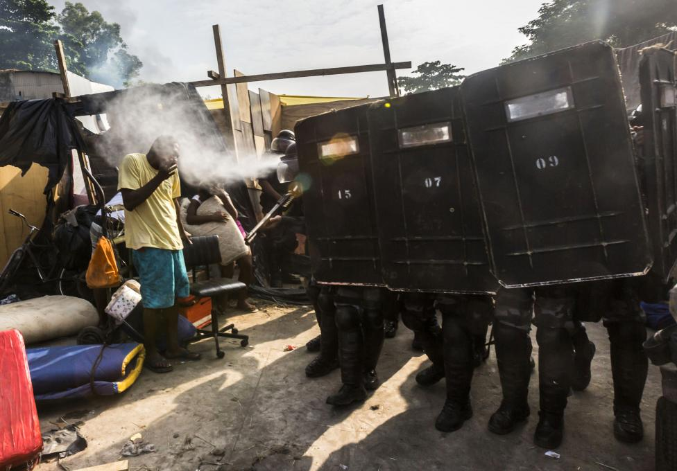 Riot police use pepper gas against residents of the Telerj slum as they attempt to repossess the land in Rio de Janeiro
