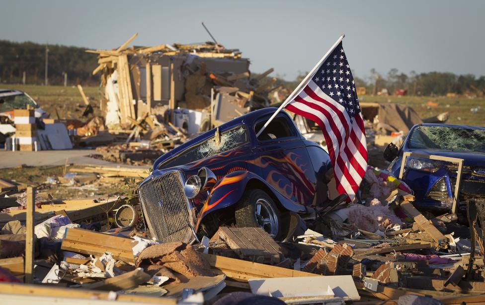 U.S. flag sticks out window of damaged hot rod car in suburban area after a tornado near Vilonia, Arkansas